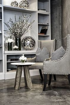 ~patterned concrete floor, leather chairs, table with reclaimed wood legs, beautifully styled shelves~