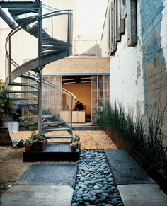 Love this narrow courtyard. The beach rocks and the spiral staircase are my favorites.