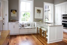 """In this kitchen a different strategy solved the problem. With a peninsula used for the sink cabinetry — set perpendicular to the wall — the whole issue of high cabinets and a low sill is avoided. A window seat, however, fits neatly under the """"problem"""" window and is balanced on the left by a standard-height cabinet."""
