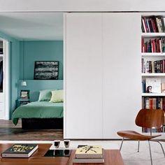 Full height sliding door reveals turquoise bedroom beyond, Remodelista