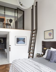 A desk from DDC and a chair by Kai Kristiansen sit in a writing nook that is accessible from the master bedroom via a ladder. The cozy area is meant to serve as a personal retreat from the city. #cityhome #cityliving #masterbedroom