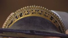 According to google translation it's a diadem of gilt brass and glass beads.