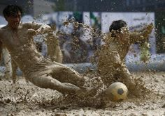Players battle for the ball during their match at a swamp soccer tournament in Beijing, June 26, 2014. REUTERS/Kim Kyung-Hoon