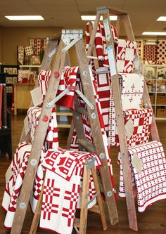 red and white quilts displayed on old wooden ladders. I need a quilt store!