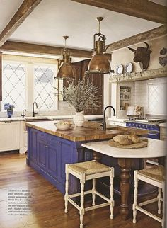 Copper farmhouse sink, copper pendants, rustic beams, blue stove and island.