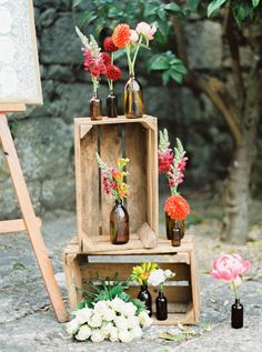 Wedding decor with crates, bottles, and bright flowers | Image by Brancoprata