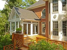 10 Inviting Porches, Balconies and Sunrooms: This porch is essentially all glass with a roof that matches the house and doors that open wide onto the deck to create a wonderful indoor/outdoor entertaining space. Photo by Patio Enclosures. From DIYnetwork.com