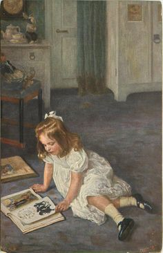 young girl in white dress, sits on floor and reads picture book