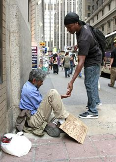 """A pedestrian gives money to a homeless man sitting outside St. Francis of Assisi Church in New York City in 2009. Poverty is """"more than an issue to be discussed or a problem to be solved,"""" the Catholic bishops of Washington state said in a joint pastoral letter Nov. 17. (CNS photo/Gregory A. Shemitz)"""