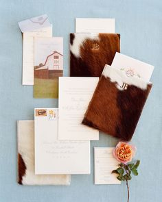 The couple's crest was printed on a card that was layered over the formal invitations, and a photo of the barn served as the cover page of the thread-bound booklet listing the weekend's schedule. #weddinginvites #weddinginvitations #weddingsationery #rusticweddinginvites | Martha Stewart Weddings - This Couple Made It Official on the Same Wyoming Ranch Where the Groom Proposed