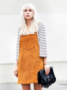 Courtney Trop wears a striped shirt, suede overall dress, and a fringe bag