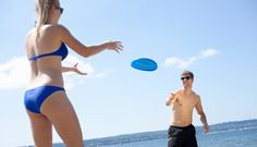 Stock Photo : Couple playing frisbee on beach