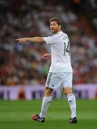 Xabi Alonso tiene el pelo rubio y el es alto. Lleva blanco. El es muy bueno en el fútbol.