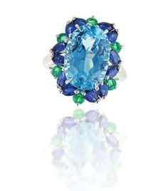 An Oscar Heyman ring set with a large aquamarine, with sapphires, emeralds and diamonds.