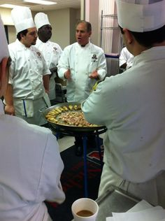 Chef John Folse explaining how a paella is made.  Historically it is also arranged in a design to mimic the stones in the patio floor of the person doing the dish.