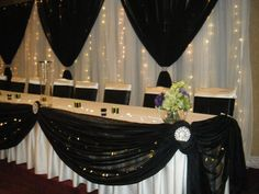 A pipe and drape backdrop with uplighting and swags, with matching table…                                                                                                                                                                                 More