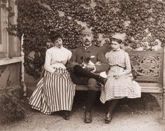 Wearing a check knickerbocker suit with ribbed three-quarter socks and low-laced oxfords and holding a terrier pup a father sits arm-in -arm between his two daughters clad in stripes, c. 1890s.