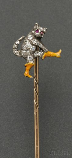 Quite charming! Antique enamel and diamond 'Puss in Boots' stickpin, the gentleman cat with old European, single-, and rose-cut diamond melee body and ruby eyes, pulling on a pair of enamel boots, silver and 14kt gold mount.