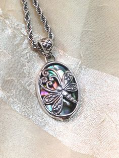 An ornate and graceful dragonfly design in sterling silver rides atop swirling colors in abalone. Very feminine and suitable for any occasion.