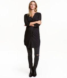 Schwarz. Knielange Tunika aus zartem Jersey. Modell mit V-Ausschnitt, Knopfleiste und Bindegürtel. Langarm. Abgerundeter Saum mit Seitenschlitzen und etwas