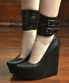 Black leather platform with a buckled ankle strap and a super pointy toe
