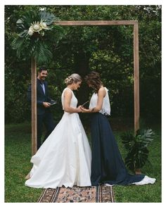 Lesbian Wedding - the contrast between the white and the black dress, and that arbor