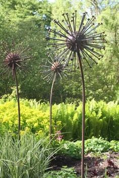 Landscape timber spikes and rebar for stems make garden flowers. Trying to figure out what was used for the sphere, tho.