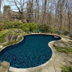 Curved pool and stone slab pool deck with accent rocks. (Source: Sotheby's Estates)