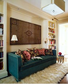 That sofa! single-cushion, teal, contrast piping. Sconces screwed into flanking bookcases, and textile hung on wall. Shag rugs make me uneasy, but I like the rest.