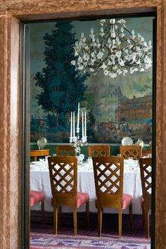 The Dining Room. It looks like the room is just large enough for the table and chairs. Delightful mural and chandelier and contrasting chair cushions. The woods tie in with the mural colors. Beautiful!