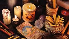 magic objects candles and the tarot cards in candle light. fortune telling seance or black magic ritual. scary still life with occult and esoteric symbols. halloween or divination rite