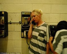An inmate uses the pay phone to reach out to loved ones while in jail, where they are allowed one hour on weekends to make calls