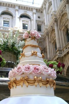 gold and white wedding cake with additional pink floral decoration