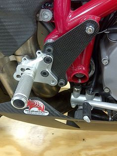 Carbon Fiber Footpeg Bracket Protector for Ducati 848, 1098, 1198 made by Dragonplate. The protector has saved the footpeg brackets on 4 bikes that I know of.