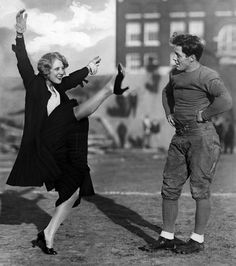 """Justine Johnstone- Musical comedy star gives helpful hints in kicking the pigskin to """"Red"""" Fitzgibbon, Halfback and start drop kicker of Creighton University, at Omaha, Nebraska"""