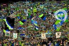 Fans raise their scarves and flags in support before the first half of the Cascadia Cup match at CenturyLink Field in Seattle.  The Cascadia Cup is the trophy created in 2004 by supporters of the Portland Timbers, Seattle Sounders, and Vancouver Whitecaps, awarded each year to the best soccer team in the Pacific Northwest. (Jordan Stead, seattlepi.com)