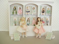 """CHOOSING A NEW DOLL The girls are about 4"""" high and their dollies are one and a half inches."""