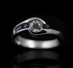 Custom engagement ring with a .53ct round diamond and four channel set sapphires graduating from light to dark blue