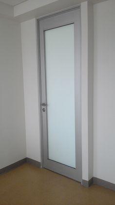 Puerta abatible con perfiles altos, chapa de seguridad y manijas de acero inoxidable. Aluminio y cristal.