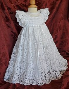 This unique Christening/Blessing dress is crocheted with #10 white cotton thread & accented with white ribbon around the waist. The detail of the bodice is adorned with rows of Popcorn stitching with a rounded neclkline of delicate crocheted lace.  The bodice is finished with short, frilly sleeves.