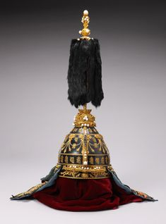 Emperor's helmet China, 1736-1795 Qianlong period  Silk, cotton, pearl, gold, bronze, other metal.  Palace Museum Beijing  The Sanskrit magic formulae on the helmet are from Tibetan Buddhism, indicating that the emperor saw himself as the supreme ruler of a multi-ethnic empire.
