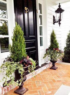 Black high-gloss front door with autumn urns