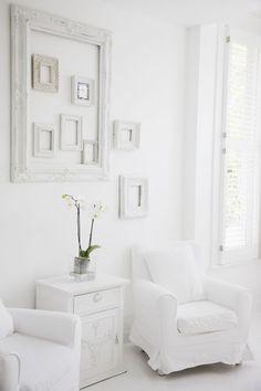 Mur de cadre blanc sur fond blanc : l'invisible decoration dans un salon tout blanc du fauteuil au buffet