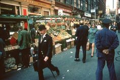 Suited and booted in Soho- A man wearing a bowler hat and carrying an umbrella walks past fruit and vegetable market stalls in Soho, London, October 1970 - Flashbak London Now, Old London, London Life, London Pictures, London Photos, Berwick Street, London History, Bowler Hat, Big Ben London