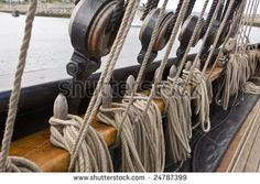 old rigging along a side of an old tall ship - stock photo