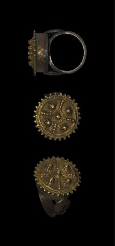 BYZANTINE FILIGREE AND GRANULE FINGER RING Circa 10th century AD. A substantial finger ring comprising a cast flat-section hoop with running loop motif between everted edges; on the shoulders, two discoid panels with central boss and radiating lines; the bezel fabricated with cast plaited sides and upper surface discoid with faux-granule decoration formed as an outer ring of filigree