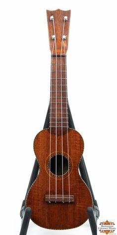 """All solid mahogany soprano uke from Oscar Schmidt. Marquetry around the top, sound hole, and back-strip. Inside, a large yellow label features a uke-strumming hula gal, and reads: """"Manufactured by OSCAR SCHMIDT, Jersey City, NJ."""" Repaired crack on the top. Rosewood fingerboard"""