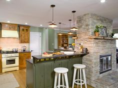 This rustic kitchen space features a large painted green kitchen island with a gray stone fireplace that acts as a divider between the two breakfast bar areas. White stools and several pendant lights add modern touches to the space, while a vintage stove lends a retro vibe.