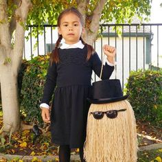 I turned my daughter's plastic pumpkin into a Cousin It trick or treat bucket to match her Wednesday Addams Halloween costume. The tutorial is on the blog today! #halloween #costume #AddamsFamily #wednesdayaddams #cousinit #diy #diyinspireddotcom #trickortreat #bhgcelebrate