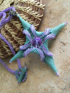 Stunning colors of sea glass green and violet make this twisted star pendant a standout piece of jewelry. I created it using Delica and glass round